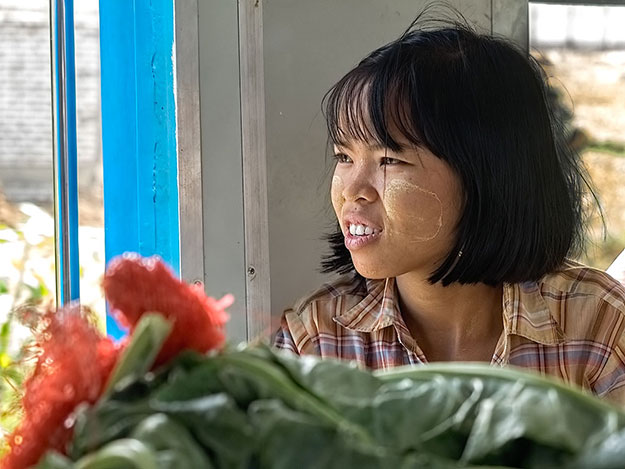 After loading produce onto the train, this young girl enjoys the scenery