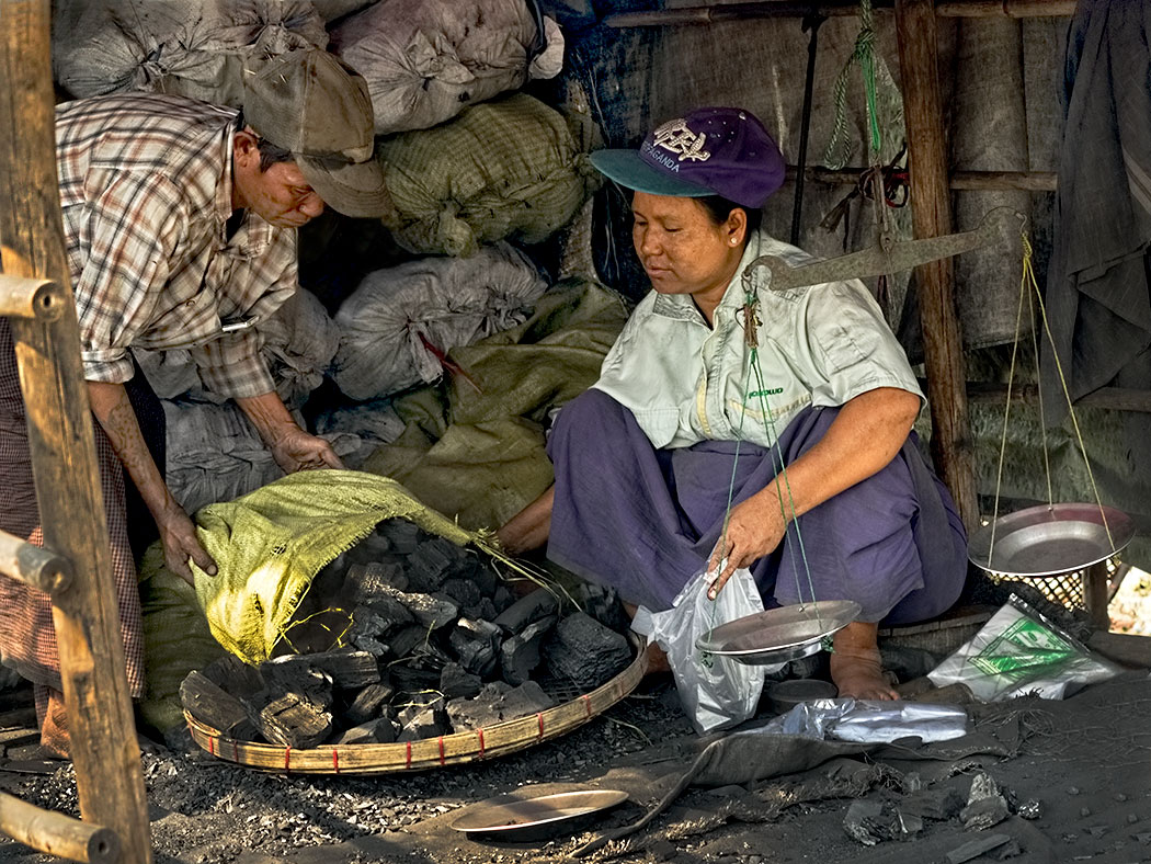 Unloading bags of charcoal at the market in Dala, a small village across the river from downtown Yangon, Myanmar