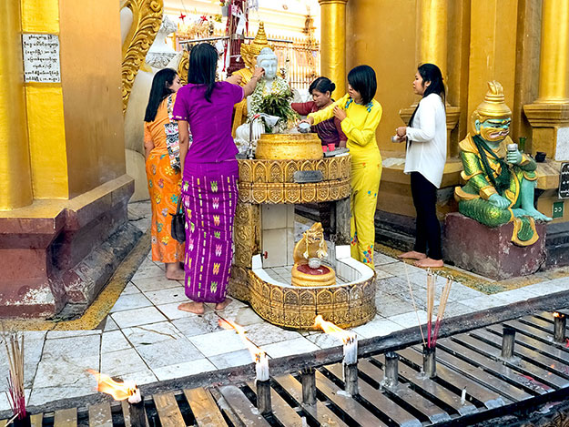 "Women ""wash"" the Buddha by pouring water over a marble carving of him, thereby earning merit"