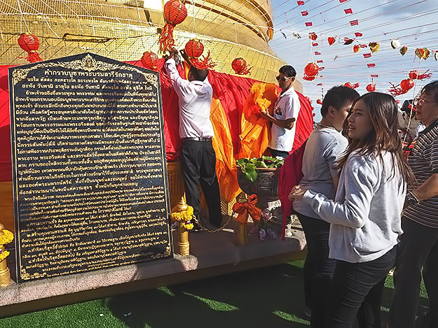 Workers drape the stupa with colored silk upon which donors have written their names