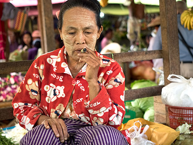 Vendor in the market at Nyung Shwe, near Inle Lake, Myanmar, smokes one of the Cheroots she sells