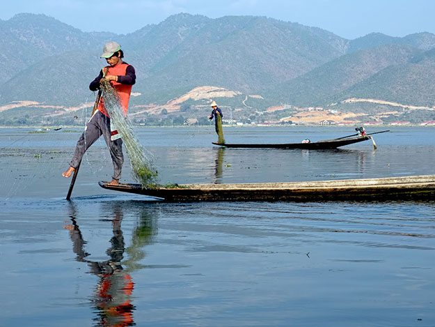 Traditional fishermen on Inle Lake balance on one leg at the front of their boats, rowing with a paddle attached to the other leg. The elevated position allows them to navigate through dense vegetation that grows in the shallow lake waters.