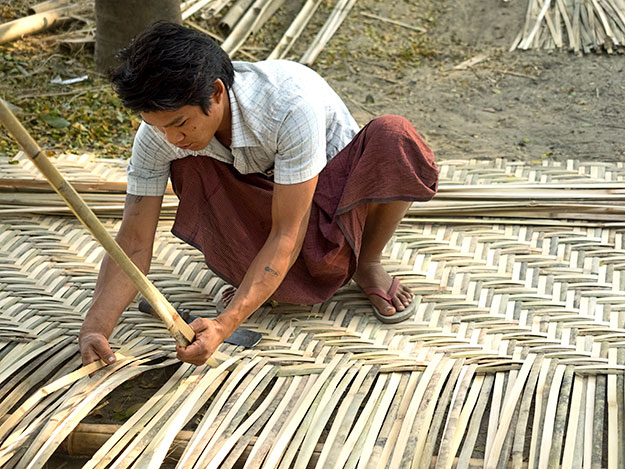"Worker weaves bamboo mats from lengths of split bamboo, which are then used in the construction of walls for homes. These ""walls"" can last up to 20 years in areas of the country that do not get much rain."