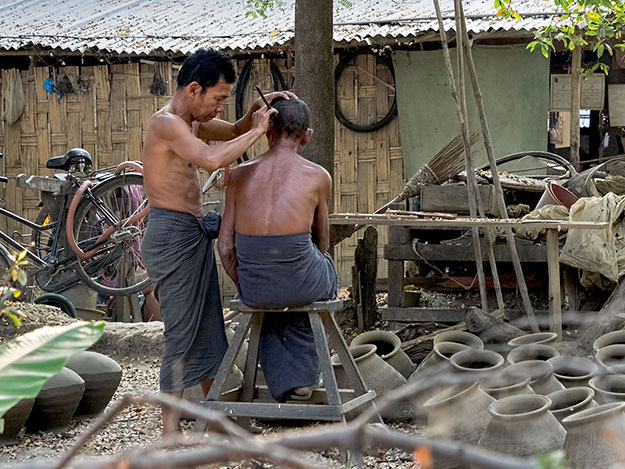 Backyard barber in the pottery-making village of Yandabo. The men are wearing traditional longyi, long tubes of fabric that are knotted around the waist.
