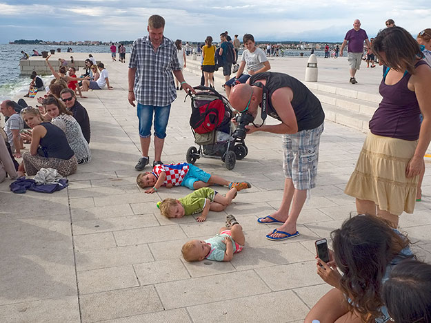 Children press their ears to the pipes of the Sea Organ on the Riva in Zadar