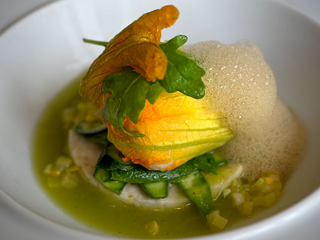 First Course of the Melon Menu at Restaurant Prévôt: zucchini flower stuffed with mousse of prawns and hake fish with yellow zucchini, on a bed of fresh zucchini soup with verbena, topped with foam of the crustacean