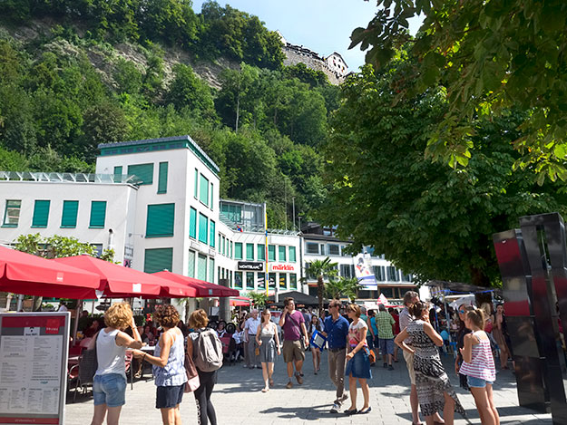 People from all over the world come to enjoy the festivities during National Day in Liechtenstein. Note the castle of the Prince of Liechtenstein on the top of the hill, overlooking the capital of Vaduz.