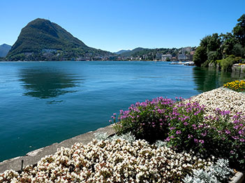 Monte San Salvatore rises on one side of the crescent bay where the town of Lugano, Switzerland graces the shores of Lake Lugano