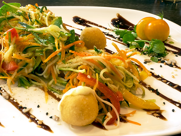 Julienne vegetables with fried cheese balls at Fat Pumpkin Vegetarian Restaurant in Riga, Latvia