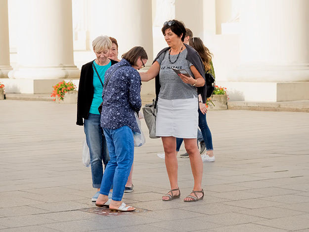 "Tourists in Vilnius twirl around three times on the Stebuklas ""miracle"" tile in hopes that their wishes will be granted"