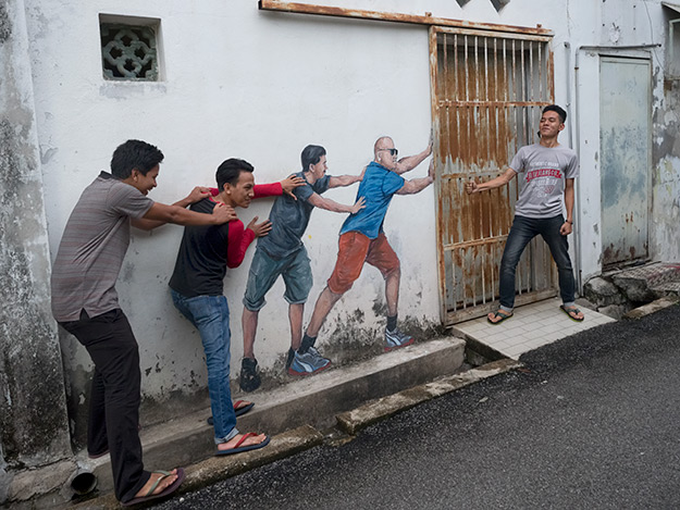 Visitors interact with this untitled street art in George Town, located in an alley off Armenian Street