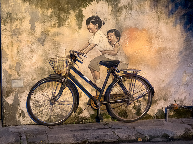 """""""Little Children on a Bicycle"""" uses an actual old bicycle to create the three-dimensional piece. Located on Armenian Street."""