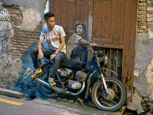 "Tourists in search of street art in George Town often perch on this real motorcycle to become part of the painting. Located on Ah Quee Street, it is titled ""Boy on a Bike."""