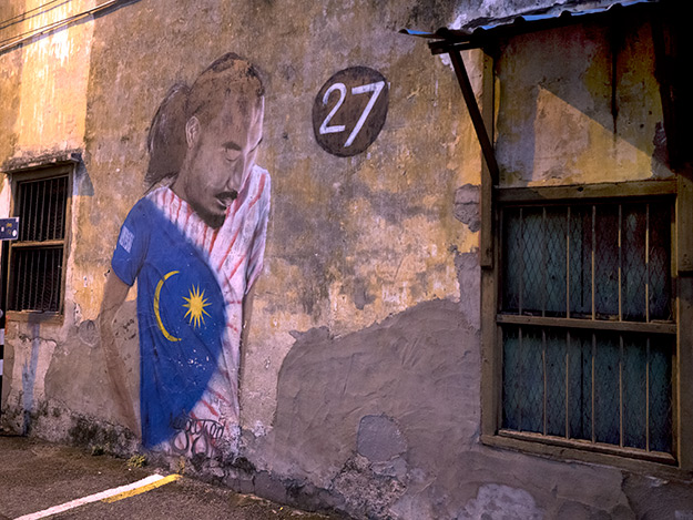 "Titled ""Malaysian Man in a Flag Shirt."" There seems to be a mystery surrounding the number 27 that is painted next to the figure, which is located on Ah Quee Street."