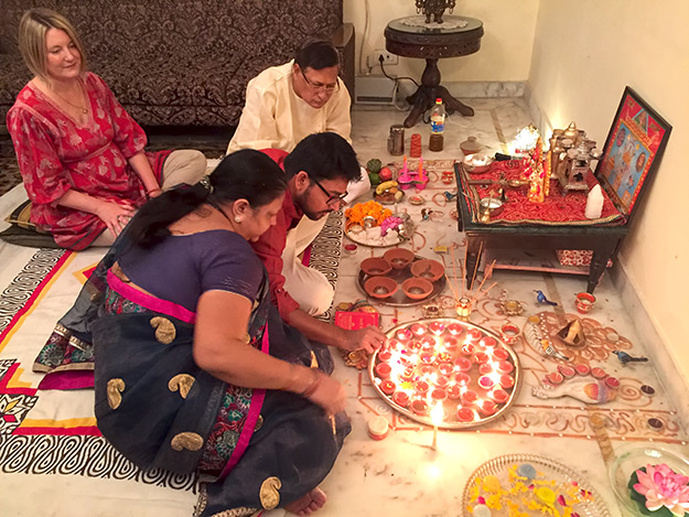 Gupta family and guest Mariellen Ward light candles at the Diwali Mandir
