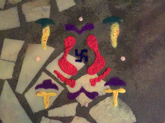 Rangoli with footprints made of colored powder shows the gods the way to the house