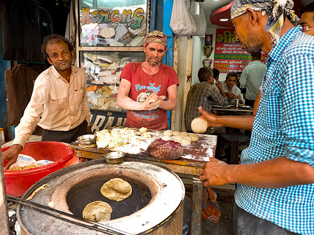 Men make paratha in an open oven on the streets of Old Delhi, India