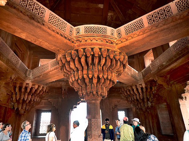 A profusely carved column topped by a colossal bracketed capital inside the Jewel House at Fatehpur Sikri