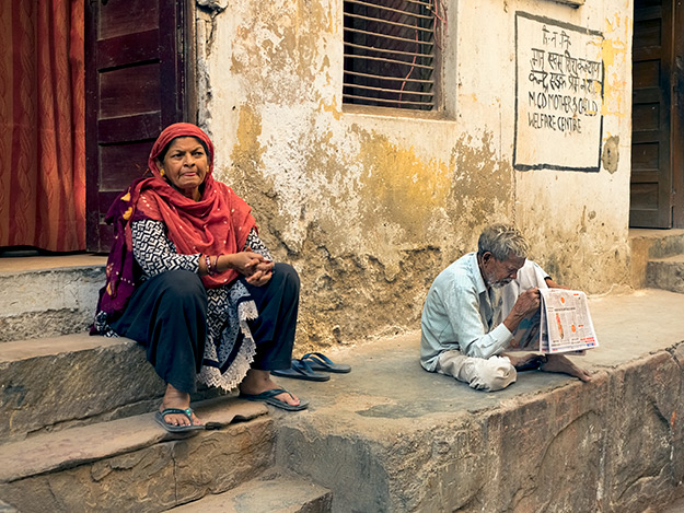 Beneath a scorching sun, men sit on stoops, squinting at the daily newspaper in Delhi India