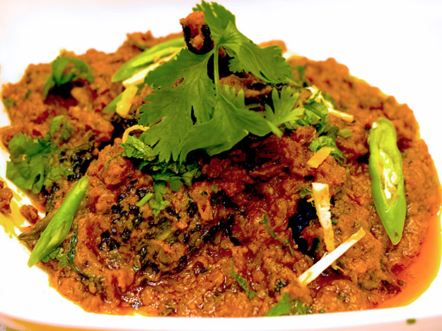 Bitter gourd stuffed with chopped onion masala curry garnished with cilantro green chilies and mint at DoubleTree by Hilton in Agra, India