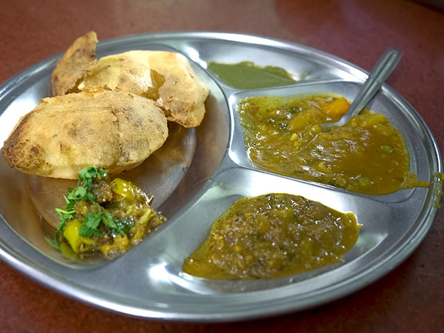 A mini Thali plate with coriander chutney, sweet potato curry, dal vegetable curry, and masala puri in the old market in Agra, India