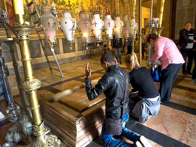 Worshipers inside Church of the Holy Sepulchre in the Holy City of Jerusalem pray at the stone slab where Jesus' body was anointed with oil prior to being entombed