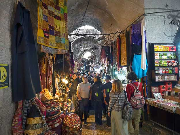 Shops line both sides of the dark narrow alleyways inside the Muslim Quarter of the Old City of Jerusalem