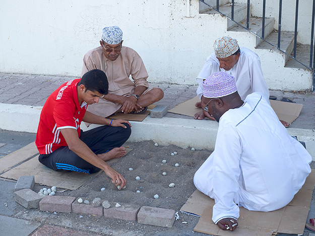 Omani men play Hawalis, a board game where stones are moved between four rows of cups dug in the sand. This version of the game is said to be exclusive to Oman