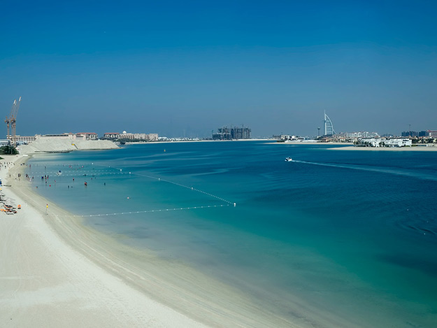 """One of the channels that create the """"palm fronds' on the artificial island known as Palm Jumeirah. The magnificent sail-shaped Burj Al Arab Hotel is seen on the horizon."""