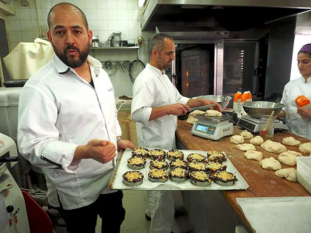 Itzik Kadosh, co-owner of Kadosh Cafe, shows off his pastries in the kitchen