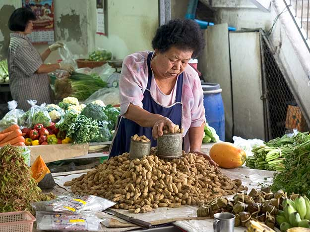 Vendor at the Chiang Mai morning market measures out roasted peanuts