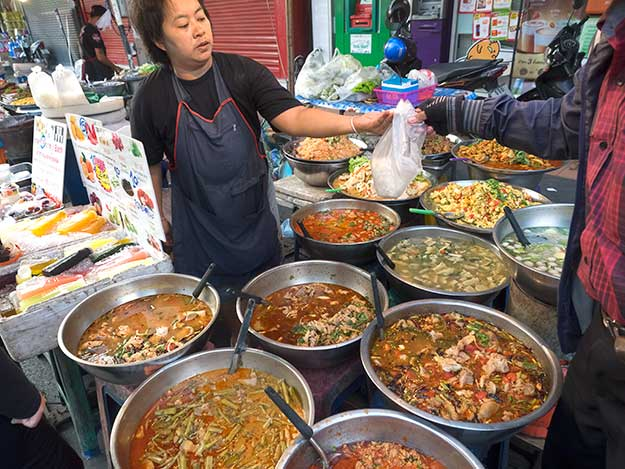 Customers take away dinner in a plastic bag at Chiang Mai Gate night market