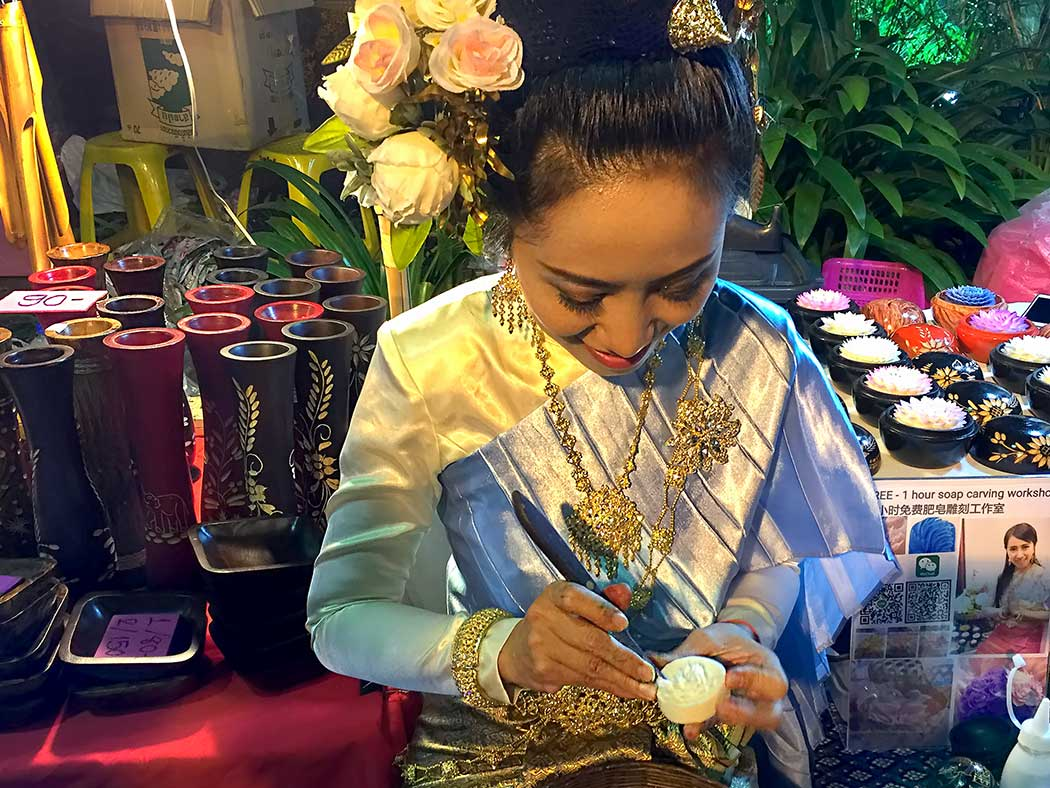 This woman at the Sunday night Walking Street Market in Chiang Mai is demonstrating the art of soap carving in Thailand