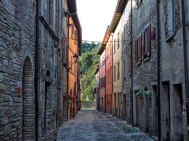 Ancient stone buildings mingle with brightly painted facades in the commune of Mercatello sul Metauro in the Le Marche province of Italy