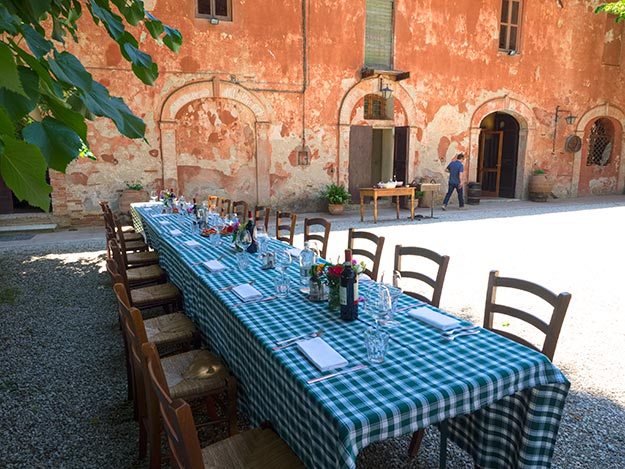 Table in the main courtyard awaits our lunch at Montestigliano holiday farm in Tuscany
