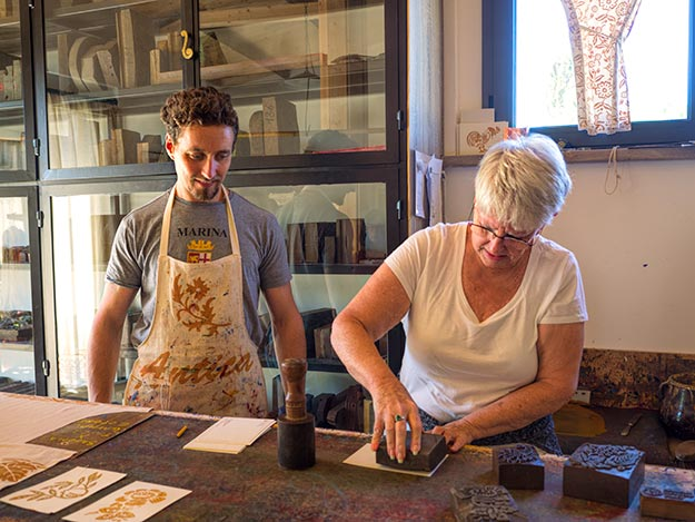 Making a postcard with antique wooden stamps at Antica Stamperia Carpegna