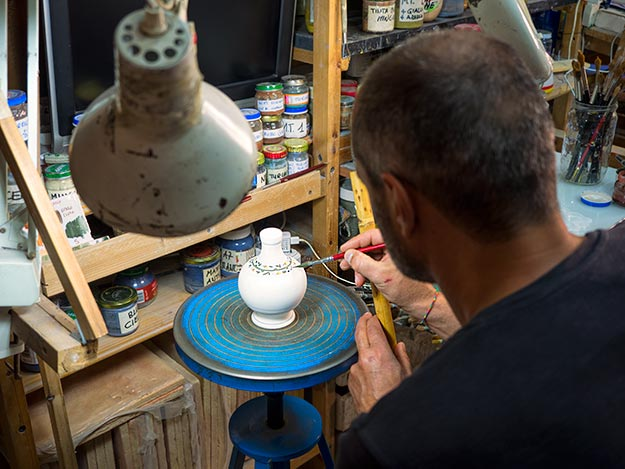 Gilberto Galavotti paints design on a vase at La Bottega Ceramiche d'Arte in Urbania, Italy