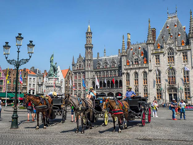 horse drawn carriages in front of provincial hof on markt square in bruge