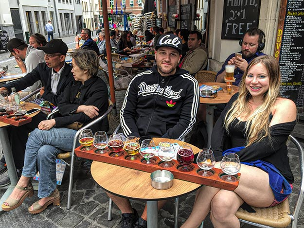 American couple in Brussels enjoy a beer flight at a curbside table