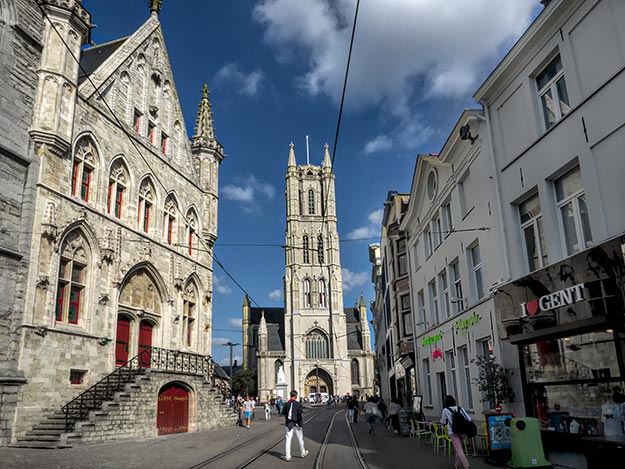 "The Bell Tower (left) and Saint Bavo Cathedral (center) in Ghent. The church is home to the famed ""Adoration of the Mystic Lamb"" (also known as the Ghent Altarpiece) by Jan and Hubert van Eyck"