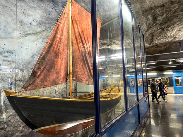 At Fridhemsplan station, a small Swedish sailing boat known as a blekingeeka is displayed in a glass case