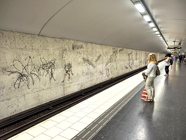 At Ostermalmstorg station, stylized charcoal sketches promoting the themes of women's rights, peace, and the environment