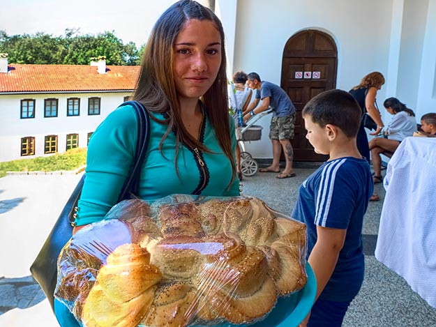 Woman at Klisurski Monastery carries Pogacha bread that will be served after the baptism