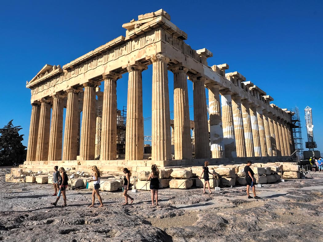 The ancient Parthenon, a classic Greek temple to the goddess Athena, perches atop a massive rock outcropping in the center of Athens, Greece