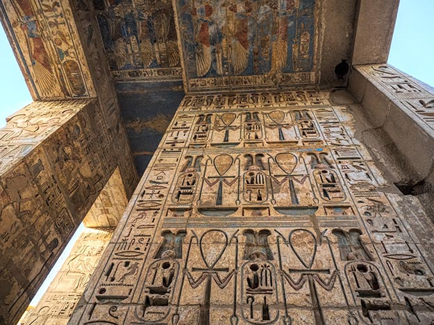 Vivid colors and intricate carvings on the walls of Medinet Habu, the Mortuary Temple of Ramesses III, one of the best preserved tombs of Luxor, Egypt