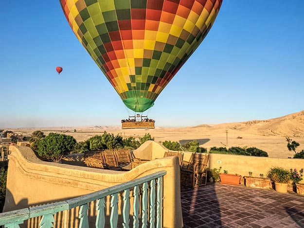 Hot air balloon floats over Beit Sabee Guest Huse in Luxor, Egypt