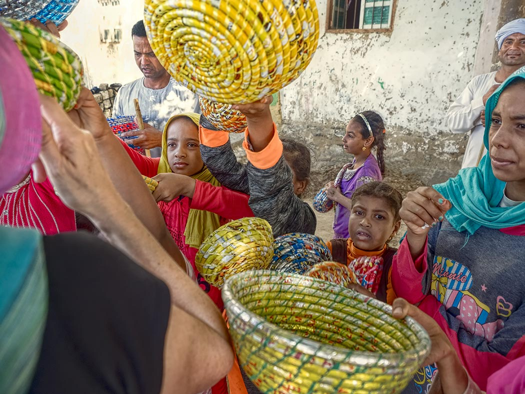 At El Kab, Egypt, children sell baskets they make from candy wrappers