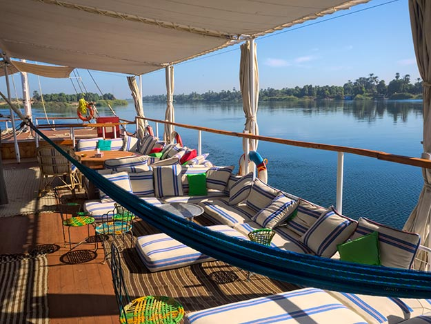 Soaking up the golden afternoon light while El Nil is tied up to a lush green island in the center of the Nile River