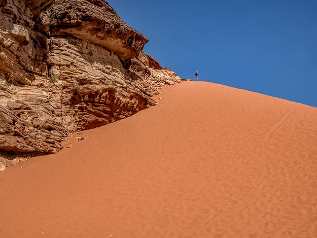 Tiny figure of a man stands atop a massive red sand dune in Wadi Rum, Jordan