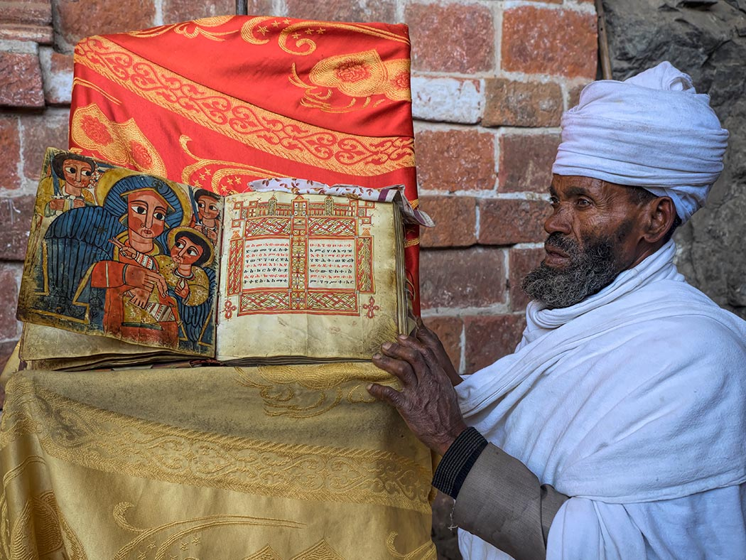 Orthodox Christian priest at Monastery Church of Neakutoleab in Lalibela, Ethiopia, shows me 500-year oldMiracle of St. Mary book, printed on goatskin